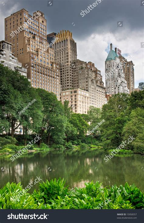 A Pond In Central Park With High Rise Buildings Behind It
